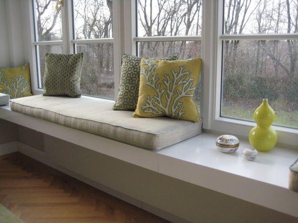 Sitzbank mit Kissen im Korallen-Design - im Hintergrund Aussicht auf Garten