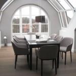 Design Esstisch mit 8 grauen Stühlen vor großzügiger Fensterfront in München