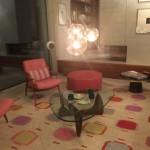 Designteppich in beige, rot, lila, gelb mit Tisch, Lampen und roten Stühlen Loher interiors Munich